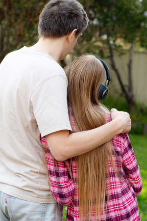 Father hug his teenage daughter who is wearing headphones. Parents and teens relationship.