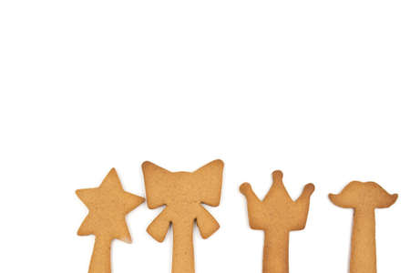 Homemade gingerbread cookies: star, bow, crown and moustache on a stick isolated on a white background. Empty space for text input