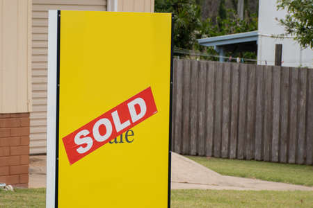 Yellow for sale sign near the resedential building house with sold sticker on it