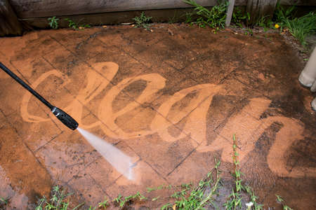 Cleaning backyard paving tiles with pressure washer. Spring clean up
