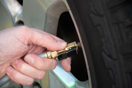 Hand holding pressure gauge, checking air pressure and filling air in the tires of the car. Car maintenance. Checking tyre air pressure before travel