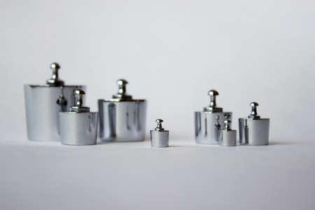 Metalen gewichten op een witte achtergrond. Metrologie en metingen gereedschappen.