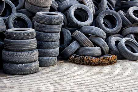 dirty car: Waste of used car tires in the tire repair shop yard with a copy space.  Stock Photo