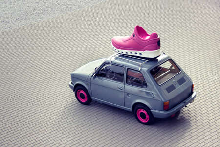 Little fashionable old car with pink sport shoe on top.