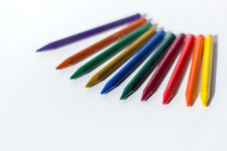 A row of colorful crayon pencil on white background with blank space.
