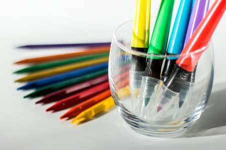 Drawing utensils - colorful crayon pencil and markers in a glass holder on white background. Stock Photo