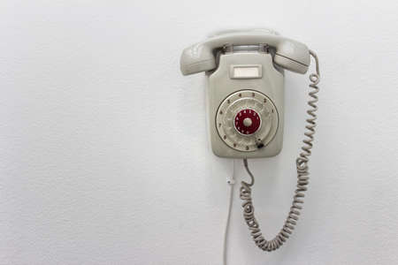 Old fashioned gray rotary telephone hanging on white wall. Stock Photo