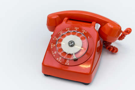 Old fashioned red rotary telephone on white background.