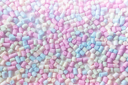 Top view of small multi colored marshmallows. Tinted with pink color background with blue, green, pink marshmallows.
