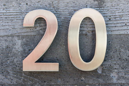 Golden metallic number 20 on textured concrete background. House number. Stock Photo