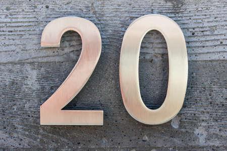Número 20 metálico dorado sobre fondo de hormigón con textura. Número de casa. Foto de archivo