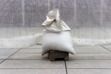 White plastic bag filled with sand and used as a weight on the outdoor reparation spot. Reparation works in the city town. Public construction zone.