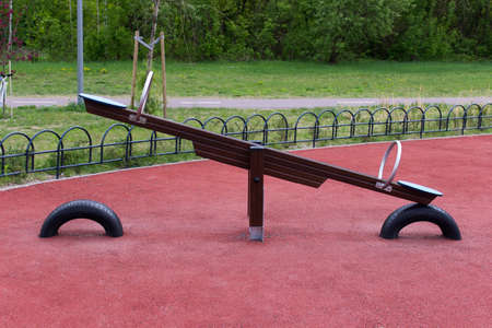 New kids playground with red floor covering and modern swing.
