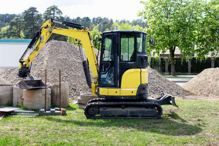 Small city excavator with scoop on construction place used for laying underground pipes. Stockfoto