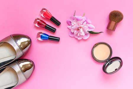 Composition with fashion accessories -  female summer flat shoes with golden decoration, one peony flower, blue red nail polishes, bronzer and facial brush arranged on pink background. Reklamní fotografie