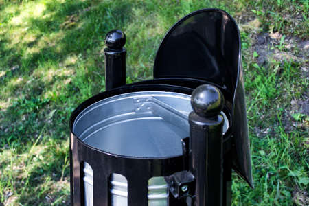 Close up of black shiny clean empty metallic outdoor trash bin, new model installed in public park . Imagens