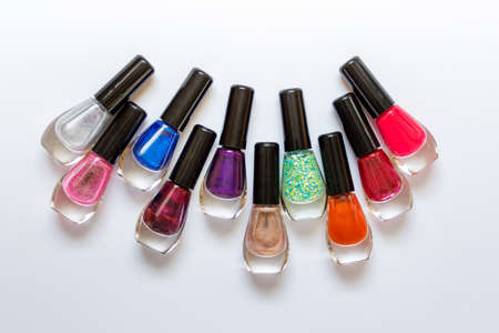 Colorful nail polishes arranged in half circle on white background.