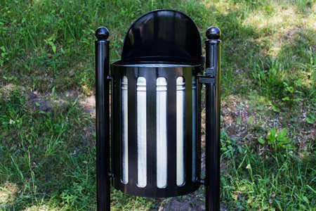 Metallic outdoor trash bin new model made of black shiny metal and installed in public park .