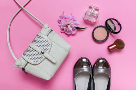 Composition with fashion accessories -  female summer small tote bag, shoes with golden decoration, one peony flower, perfume bottle, bronzer and facial brush arranged on pink background. Banco de Imagens
