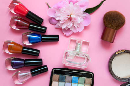 Composition with beauty fashion accessories - set of colorful nail polish, pink peony flower, facial brush, bronzer powder, eye shadows and perfume bottle. Items arranged on pink background.