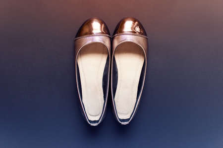 Female flat shoes with golden decoration standing on dark background. Photo tinted with orange blue gradient tint. 스톡 콘텐츠 - 124898562
