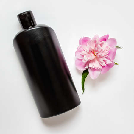Black shapoo bottle with pink peony flower on white background.