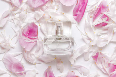 Fragrance perfume bottle with peony flowers petals on white background.