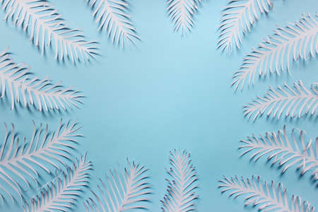 Paper handmade feathers leaves arranged in a circle on blue background. Photo with copy blank space.