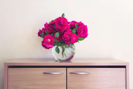 Bouquet of wild tea roses in ball glass vase standing on a cabinet.