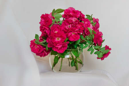 Lavish bouquet of wild tea roses in ball glass vase standing on the background of white cloth.