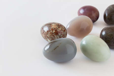 Beautiful decorative Easter eggs made of glossy polished precious opal stones colored in dark brown green colors with inclusions on white background. Photo with copy blank space. Foto de archivo - 130227992