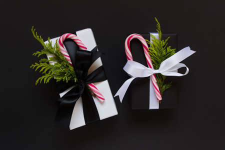 Concept simple Christmas winter greeting card with two gifts wrapped in black and white paper decorated with candy canes and fir branches on black background.