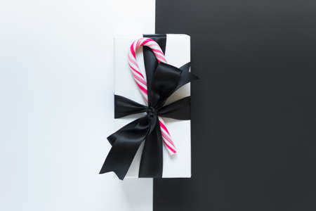 Single large Christmas New Year present wrapped in white paper with black satin bow and candy cane on duoble colored backgound.