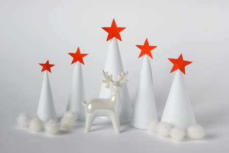 Winter Christmas new Year greeting card with concept forest made of white paper cones with red paper stars and white porcelain reindeer.
