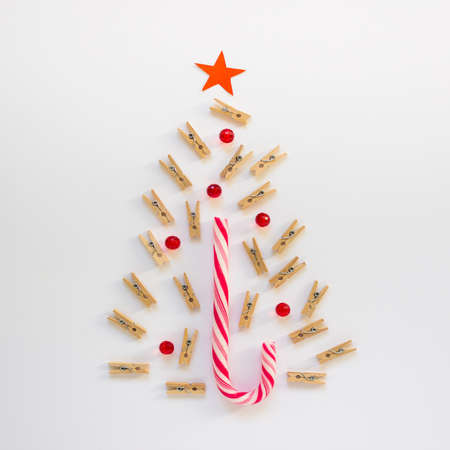 Concept Christmas tree made of little wooden pins and small red balls crystals and candy cane sweet on white background.