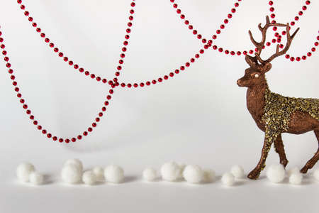 Christmas composition with hanging red ball gradlands, raindeers and white fluffy balls on white backgound. Photo with copy blank space. Stock Photo
