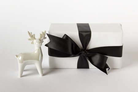 Christmas present wrapped in white paper with black satin ribbon and white porcelain reindeer on white background.