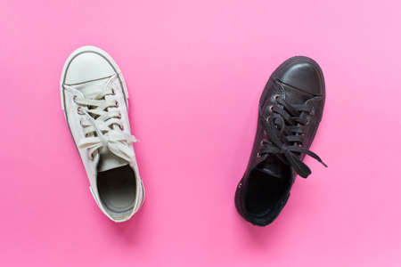 Two rubber gum sneakers shoes white and black on pink background. Concept of similarity and difference, white and black steps. Stock Photo