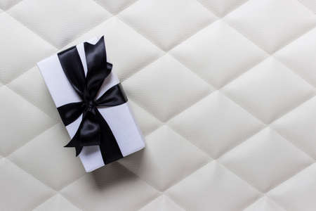 Single one present in white wrapping paper and black satin glossy bow on tufting fabric cloth background. Photo with copy blank space. Фото со стока