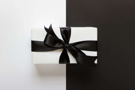 Present gift wrapped in white paper with satin black shiny ribbon on black and white background.