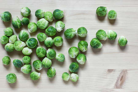 Many green brussel cabbages on wooden background arrange freely randomly.