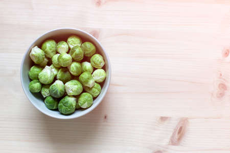 Green brussel cabbages in a bowl on wooden background. Photo with copy blank space. Reklamní fotografie