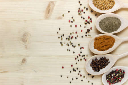 Various herbs on wooden spoons on wooden board background. Black pepper, aromatic cloves, mustard, pepper peas, paprika. Photo with copy blank space.