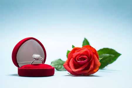 Valentine day love scene marriage engagement proposal with diamond ring and red rose.