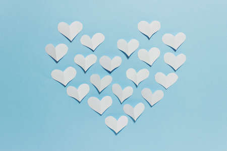 Valentine day greeting card with large heart arranged with white folded paper hearts on blue background.
