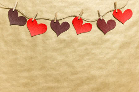 Red and dark red fabric hearts pinned to a rope on craft paper. Photo with copy blank space.