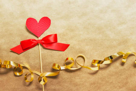 Love Valentine day greeting card with red heart on wooden stick on golden craft paper background with golden ribbon.