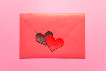 Valentines day minimalist greeting card with pink envelope and two fabric texture hearts on pink background.