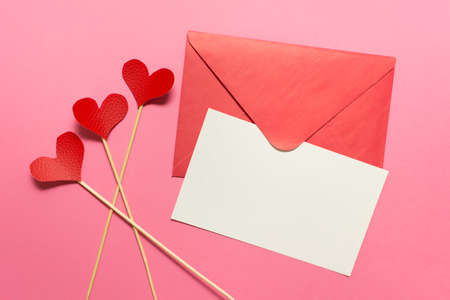 Valentine day message card with pink envelope, white card and three red hearts on pink background. Stockfoto