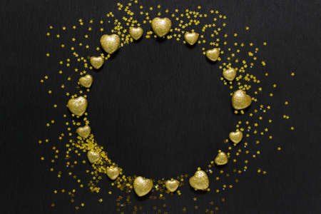 Festive Valentine day greeting card with wreath arranged of golden stars and golden glitter hearts on black background. Photo With copy blank space. Stockfoto